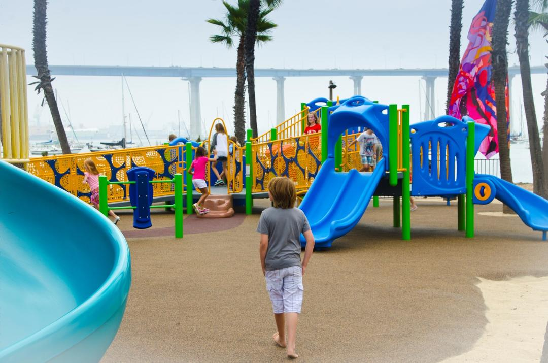 A boy child walks towards the colorful playground at Coronado Tidelands Park
