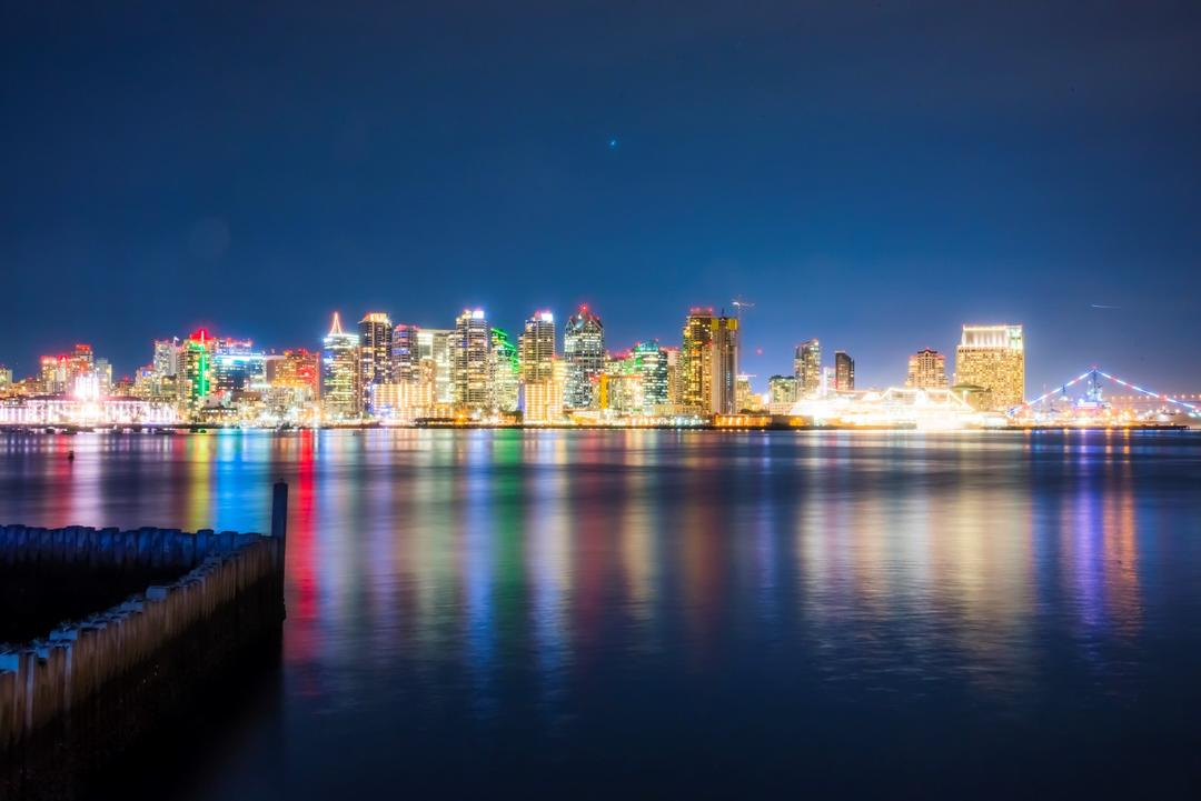 a nighttime view from Harbor Island looking towards the lit-up skyline of downtown San Diego