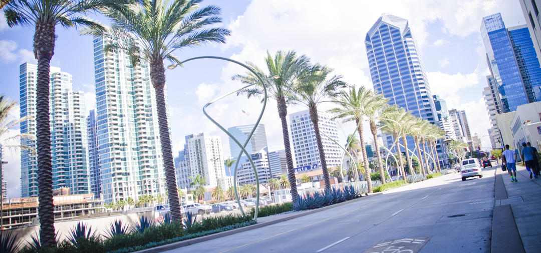 street view of Broadway, near Harbor Drive. Palm trees and spiral street lamps line the center median. Port of San Diego