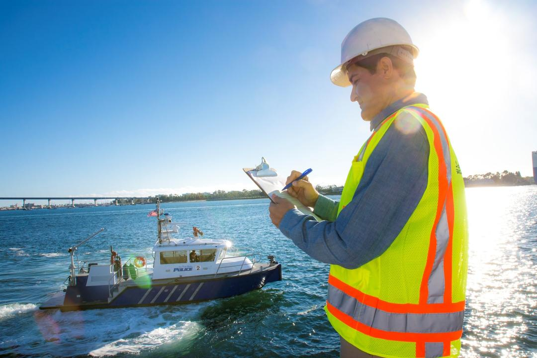 a worker takes notes on a clipboard as the Port of San Diego Harbor Police boat goes by in the San Diego Bay