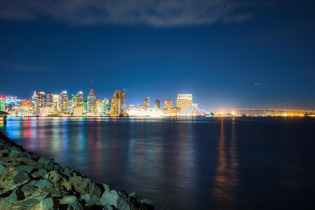 the San Diego skyline lights up at night and reflects off of the bay