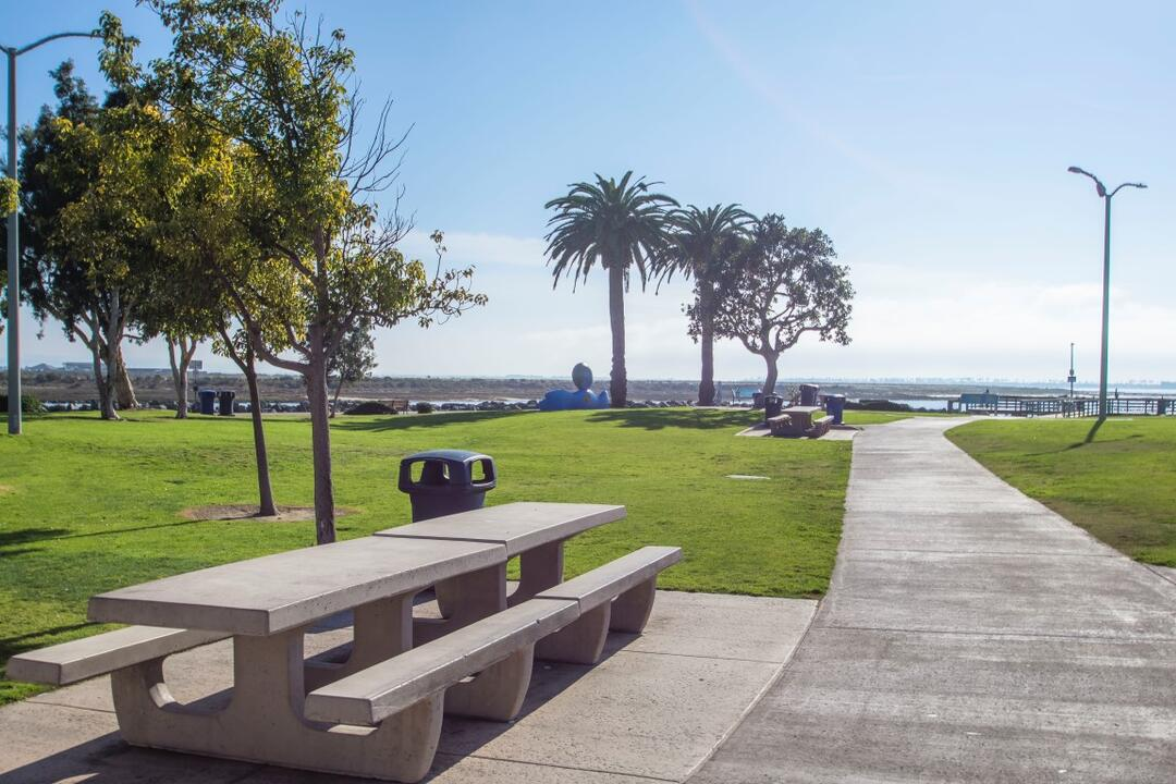 Picnic tables surrounded by green grass and trees along the path at Pepper Park at the Port of San Diego