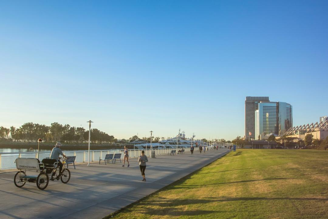 People running and cycling along the bay at San Diego Bayfront Park at the Port of San Diego
