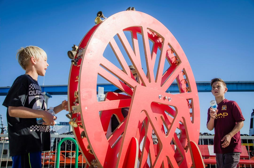two boys interact with a big red wheel at Time Strata by Margaret Noble