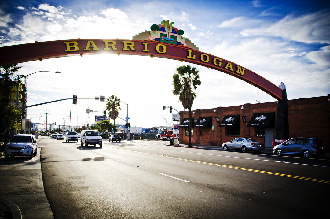 a partially cloudy day photo of the Barrio Logan Gateway sign