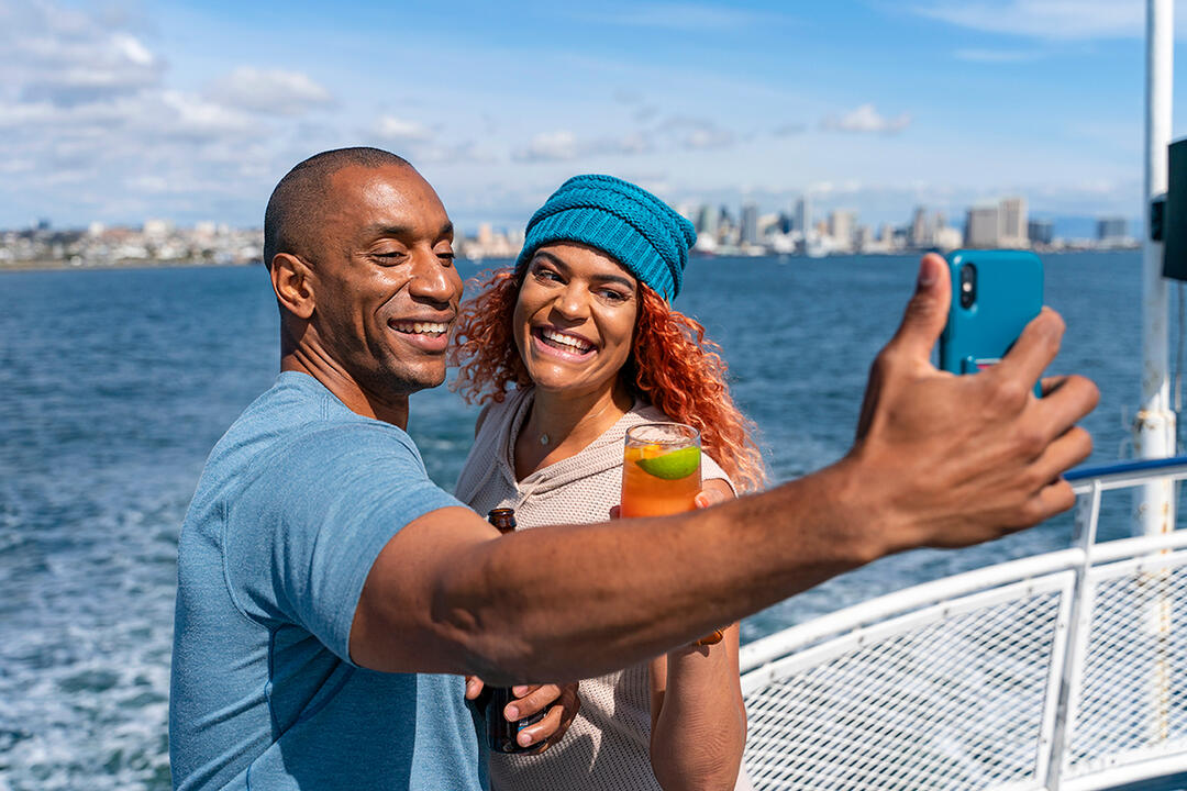 A couple takes a selfie on San Diego Bay with the city in the background - 2019