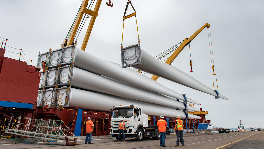 a cargo ship unloads 220 foot windmill blades at the Port of San Diego