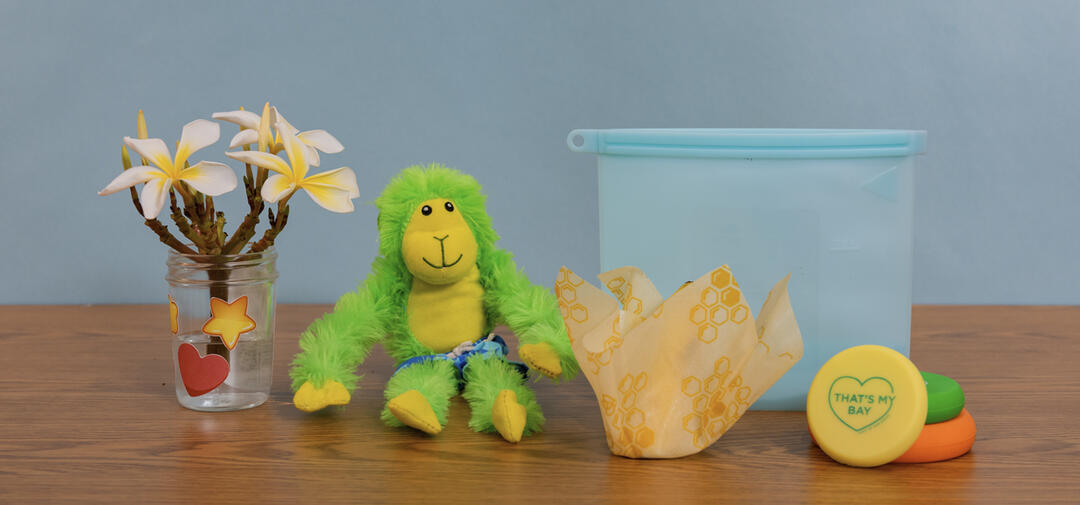 a little green monkey poses with reused items