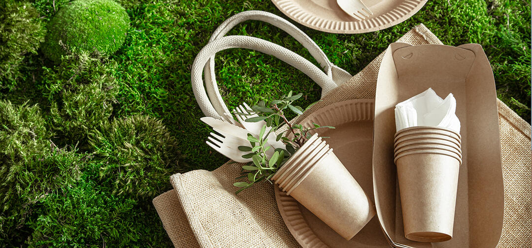 recyclable items - cups and totes, on a grassy background
