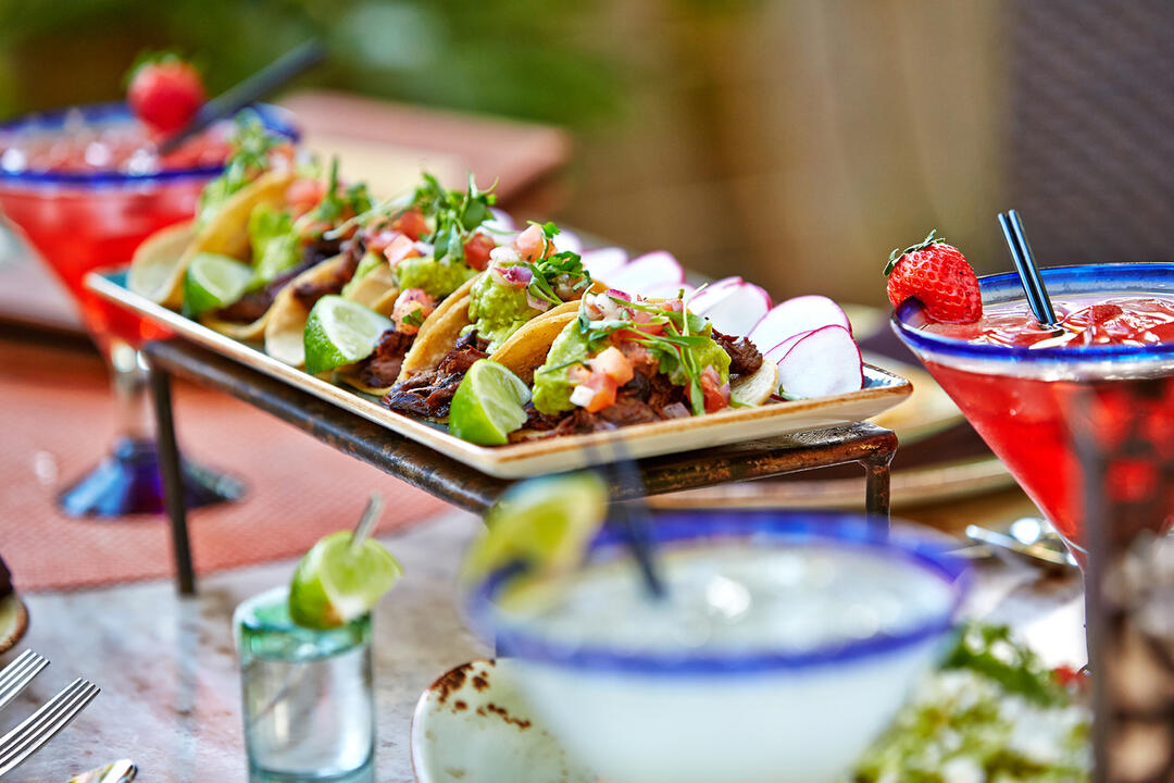Tequila Bar & Grill shows off a plate of tacos and a margarita