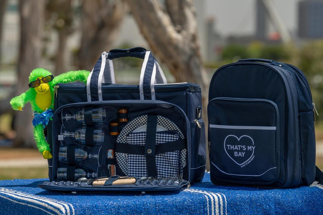 Two dark blue picnic totes, one is open and Hank, the green money, is hanging on!