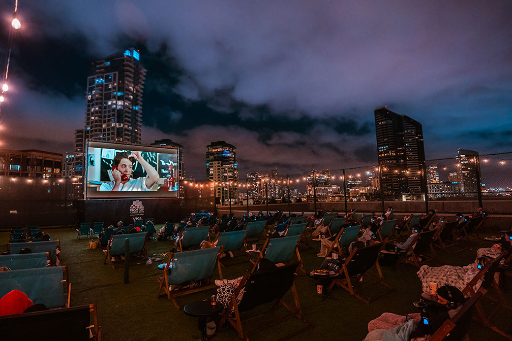 people in lounge chairs watch a movie on a roof