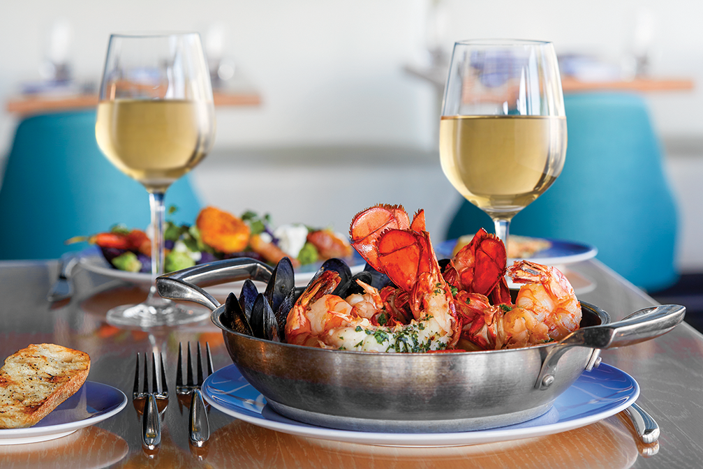 two glasses of wine sit behind a bowl of shrimp