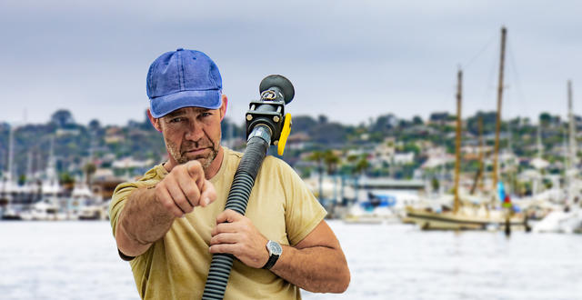 a person is holding a pump out hose and pointing at the viewer