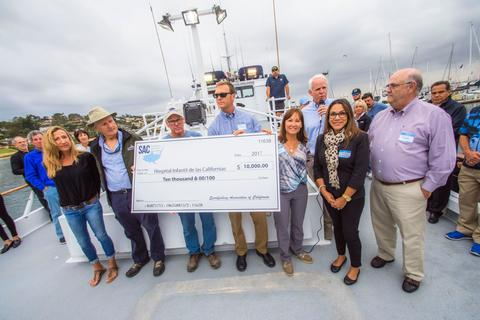 Baja Ha Ha race start- photo shows people presenting a 10,000 dollar check to help liks