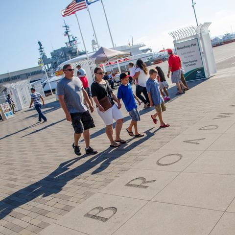 A family walks along Broadway Plaza at the Port Pavilion Broadway Pier Port of San Diego