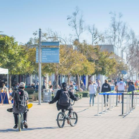 People enjoy the sun, trees and ride bikes along the Embarcadero at Broadway Plaza Park