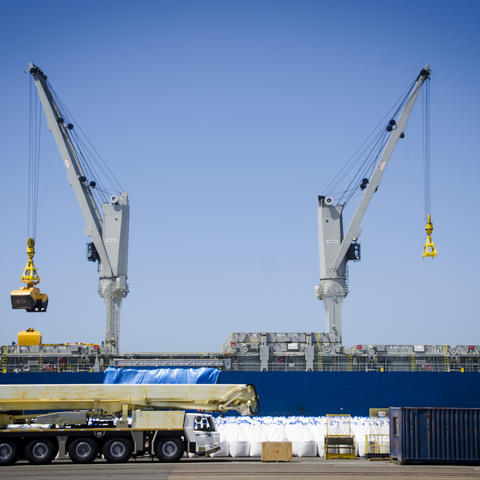 Cranes unload breakbulk sugar from ship in port at the Port of San Diego's Tenth Avenue Marine Terminal.