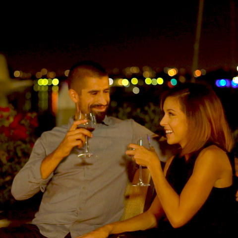 A couple enjoys a glass of wine at a fire pit at Harbor Island Port of San Diego