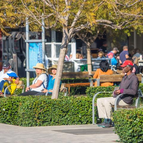 People sitting on benches under the trees and sun at Broadway Plaza at the Port of San Diego