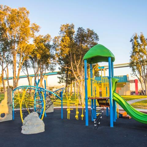 Playground with trees and Coronado Bridge in the background at Cesar Chavez Park at the Port of San Diego