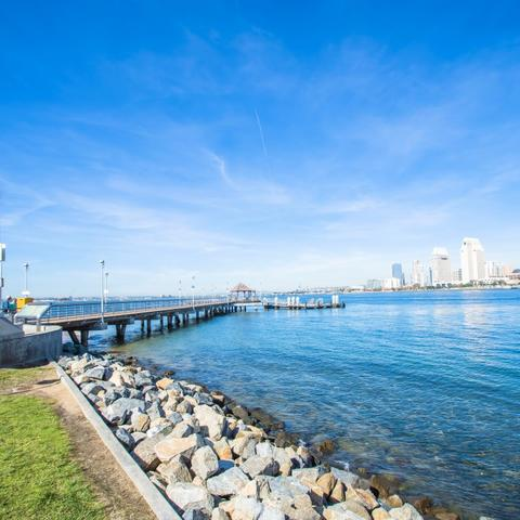 Rocks, water, pier, blue skies, and view of Downtown cityscape at Coronado Landing Park at the Port of San Diego