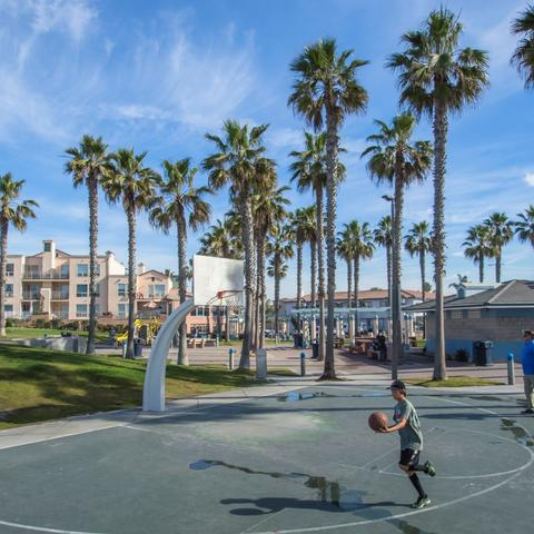 Kid playing on the basketball court at Dunes Park at the Port of San Diego