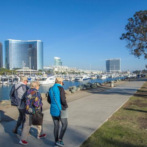 A group of people walking along Embarcadero Marina Park North at the Port of San Diego