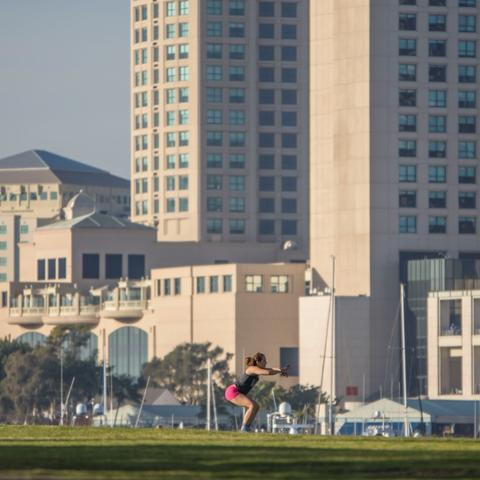 Woman working out on the grass at Embarcadero Marina Park South at the Port of San Diego