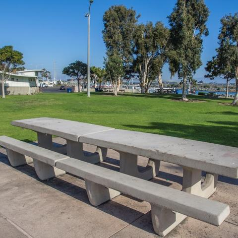Long picnic tables surrounded by green grass and trees at Pepper Park at the Port of San Diego