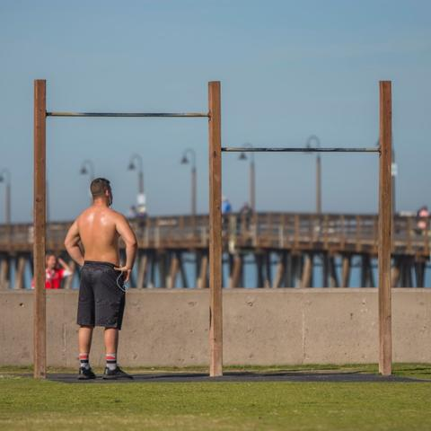 Man working out at exercise station hanging bars at Portwood Pier Plaza at the Port of San Diego