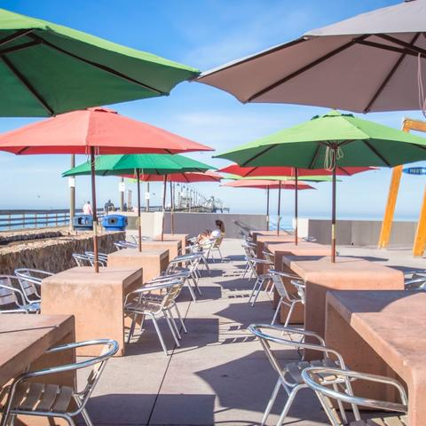 Tables with large umbrellas and chairs at Portwood Pier Plaza at the Port of San Diego