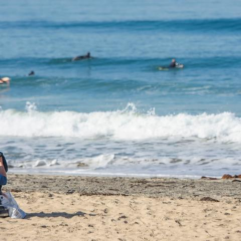 Man sitting on the sandy shore in front of surfers paddling over the waves at Portwood Pier Plaza at the Port of San Diego