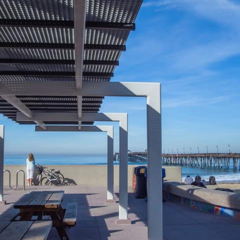 Picnic tables under awnings overlooking the beach and pier at Portwood Pier Plaza at the Port of San Diego