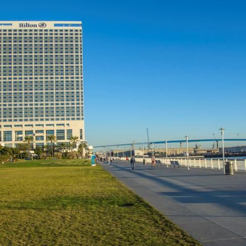 View of Hilton hotel, San Diego-Coronado Bay Bridge, grass, and path at San Diego Bayfront Park at the Port of San Diego