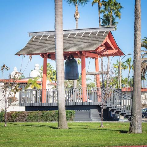Yokohama Friendship Bell surrounded by trees and grass at Shelter Island Shoreline Park at the Port of San Diego