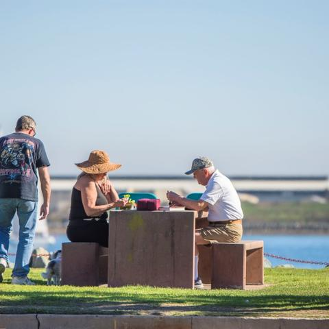 People enjoying lunch at the picnic table overlooking the water at Shelter Island Shoreline Park at the Port of San Diego