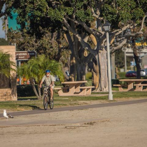 Cyclist biking past picnic tables at Spanish Landing Park at the Port of San Diego