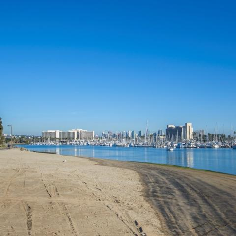 Sand beach and sparking blue water under bright blue skies at Spanish Landing Park at the Port of San Diego