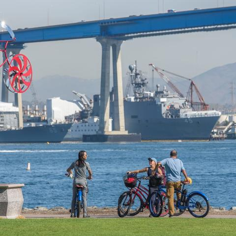 Group of cyclists in front of My Bike Sculpture by Amos Robinson at Coronado Tidelands Park at the Port of San Diego