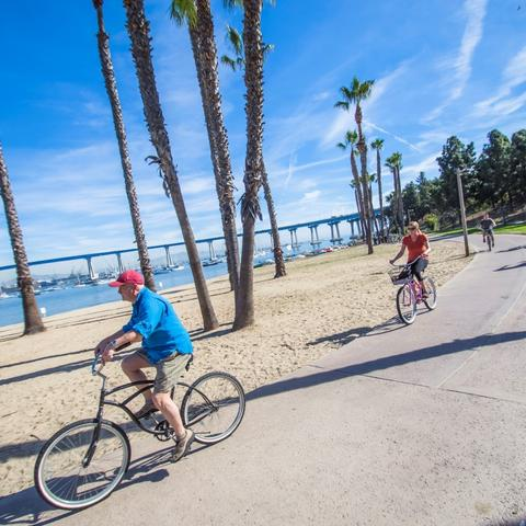 Cyclists biking on path with view of San Diego-Coronado Bay Bridge at Coronado Tidelands Park at the Port of San Diego