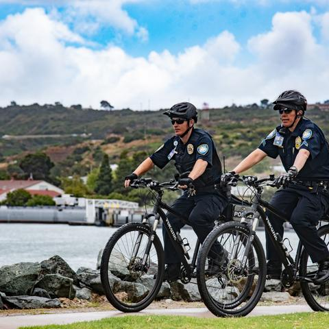 two Port of San Diego Harbor Police bike patrol in front of the bay