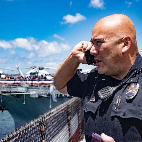 A Port of San Diego Harbor Police Officer is talking on a communication device overlooking the USS Midway