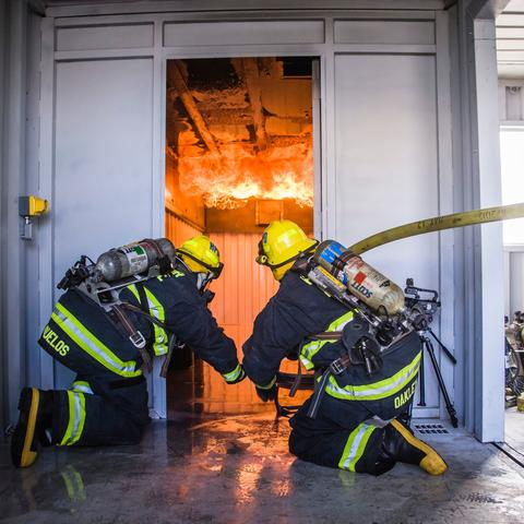 two Port of San Diego Harbor Police Firefighters training in front of a door with fire raging
